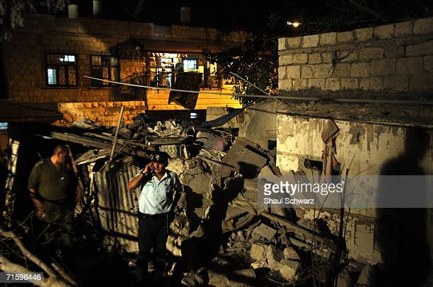 Israeli emergency personnel inspect the rubble of a collapsed building after it sustained a direct hit from a Hezbollah missile attack August 6 2006...