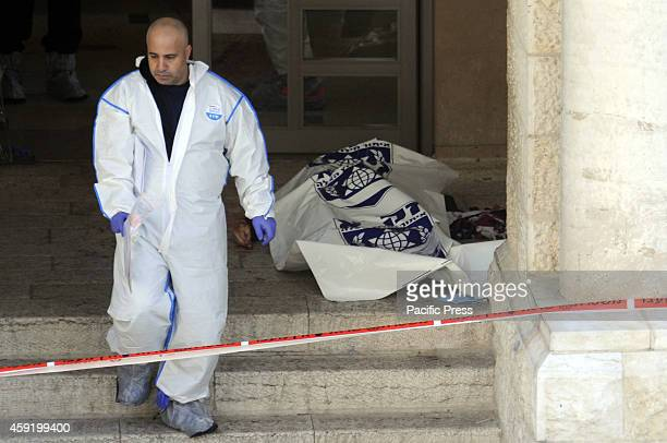 Israeli emergency personnel passed by the remains from the scene of an attack at a Jerusalem synagogue The two suspected Palestinians who carried out...