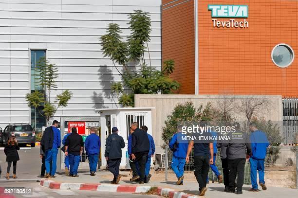 Israeli employees of Teva the world's biggest manufacturer of generic drugs walk outside the pharmaceutical company's plant in Ne'ot Hovav an...