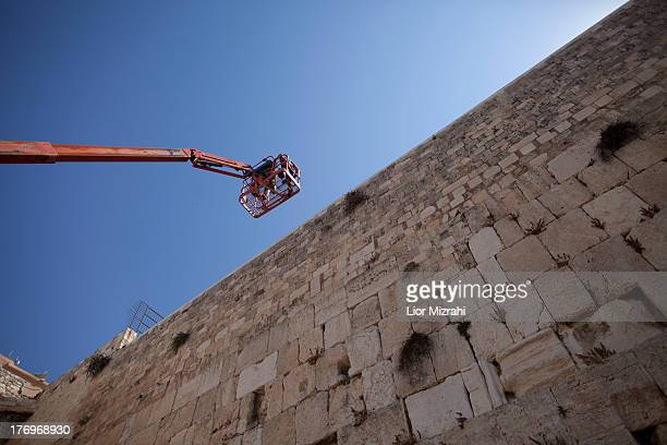 Israeli engineers on a crane check the stability of the structure of the Western Wall stones Judaism's holiest site on August 20 2013 in Jerusalem...