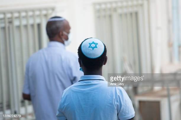 Israeli Ethiopian youth wears a Yarmulke with the Star of David symobol as he is praying outside a Jewish synagogue amid the CoronaVirus pandemic on...