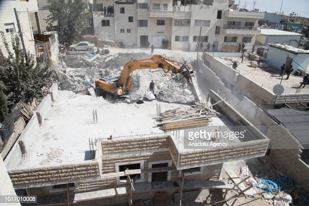 Israeli excavators demolish a Palestinian building for allegedly being unauthorized in Al-Issawiya district of East Jerusalem on August 15, 2018.