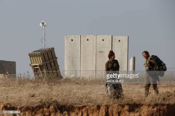 Israeli female soldiers walk near an Iron Dome defence system, designed to intercept and destroy incoming short-range rockets and artillery shells,...