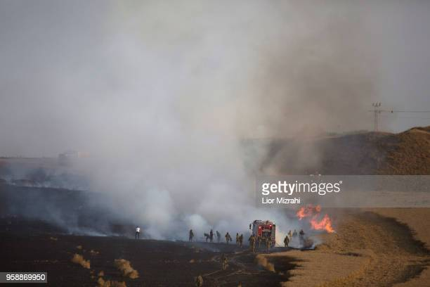 Israeli fire fighters and soldiers attempt to extinguish a fire in a wheat field next to the border with Gaza after it was caused by incendiaries...