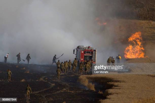 Israeli fire fighters and soldiers attempts to extinguish a fire in a wheat field next to the border with Gaza after it was caused by incendiaries...