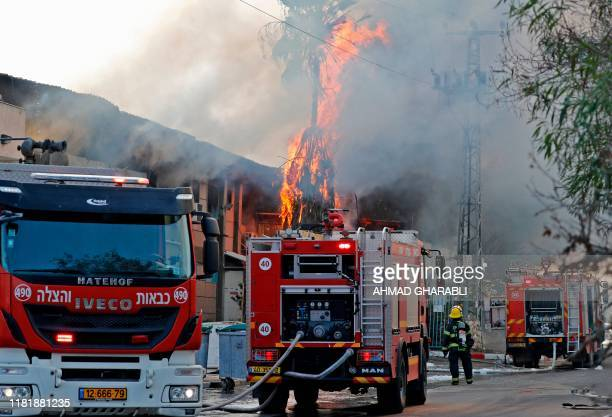 Israeli firefighter trucks douse a burning factory in the southern Israeli town of Sderot, after it was reportedly hit with rockets fired from the...