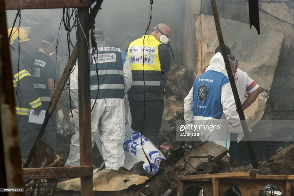 Israeli firefighters and rescue workers inspect a body after a fireworks warehouse went up in flames on March 14, 2017, in the village of Porat near Netanya. Police said two bodies were recovered from the warehouse and an investigation into the fire was continuing. /