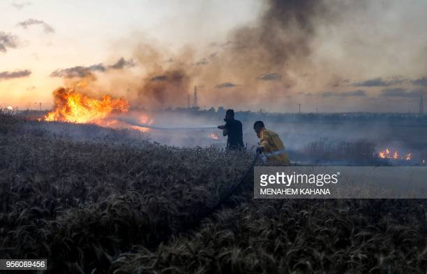 Israeli firefighters attempt to extinguish a fire in a wheat field near the Kibbutz of Nahal Oz along the border with the Gaza strip on May 8 2018...