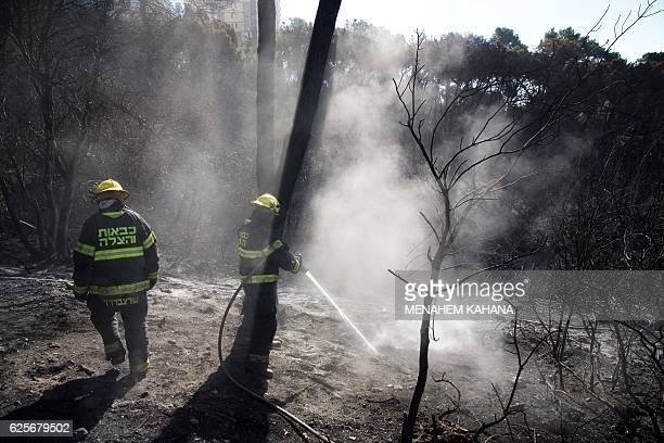 Israeli firefighters extinguish a fire in the northern Israeli city of Haifa following a wildfire on November 25 2016 Tens of thousands of Israelis...