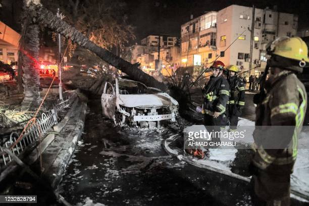 Israeli firefighters stand past extinguished burnt vehicles in Holon near Tel Aviv, on May 11 after rockets were launched towards Israel from the...