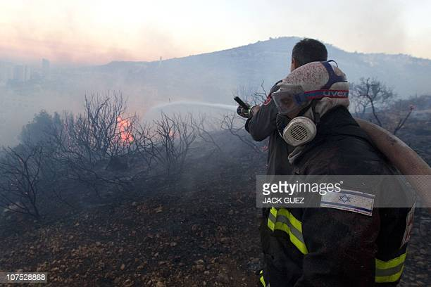 Israeli firefighters work on the slope of a burning hill in Tirat Ha Carmel near the northern city of Haifa on December 3 2010 a day after the huge...