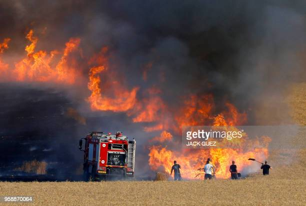 TOPSHOT Israeli firemen attempt to put out a fire in a wheat field near the Kibbutz of Nahal Oz along the border with the Gaza Strip on May 15 2018...