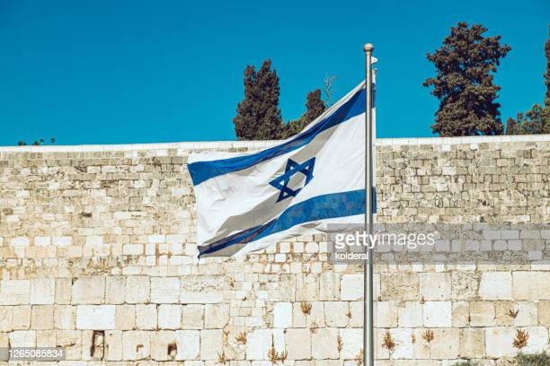 israeli flag against western wall and blue sky - israel stock pictures, royalty-free photos & images