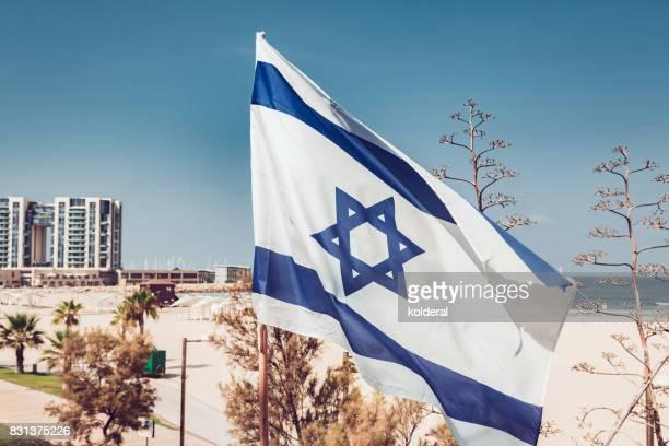 Israeli flag with Mediterranean beach on background