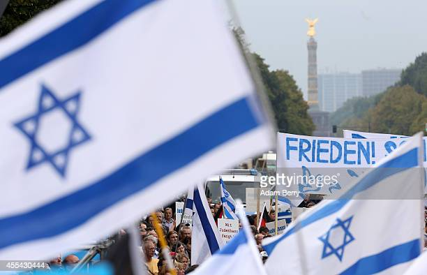 Israeli flags and a banner with the word 'Peace' in German fly in front of the Siegesaeule or Prussian Victory Column during a rally against...