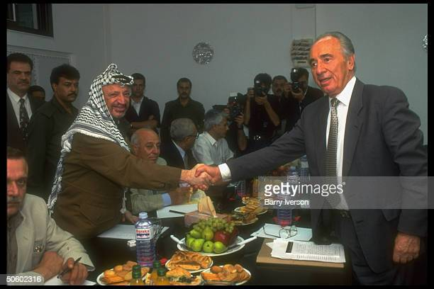 Israeli For. Min. Shimon Peres shaking hands w. PLO chmn. Yasser Arafat over table, mtg. In peace process session in Palestinian autonomous Gaza.