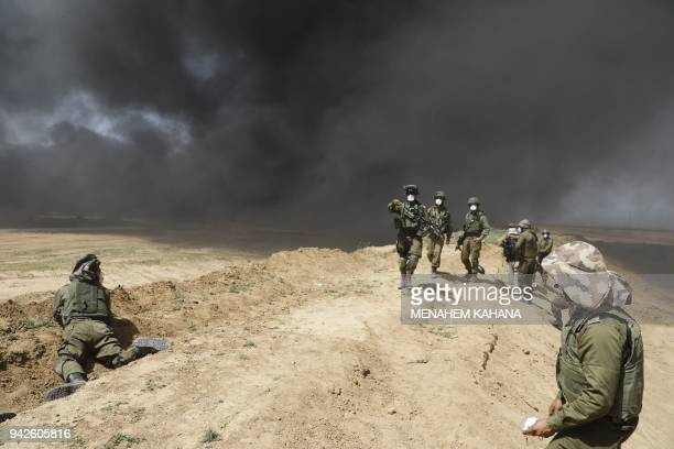 TOPSHOT Israeli forces are deployed near the kibbutz Nir Oz at the GazaIsrael border where tyre fire smoke billows from the palestinian camp of...