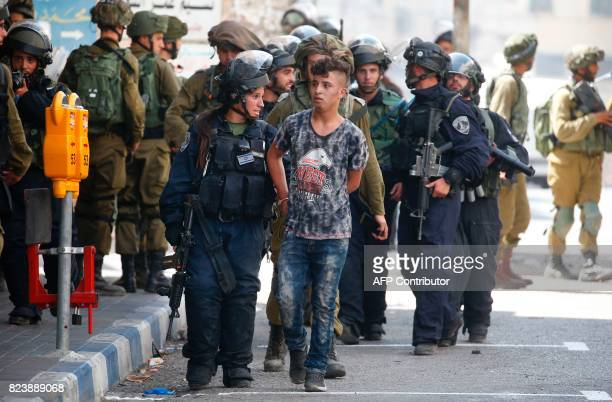 Israeli forces arrest a Palestinian youth during clashes between demonstrators and security forces in the city of Hebron in the Israelioccupied West...