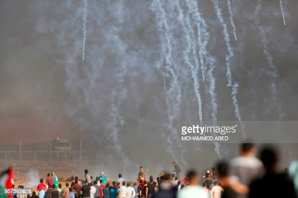 Israeli forces fire teargas canisters toward Palestinian demonstrators during clashes along the border with the Gaza strip on the eastern outskirts...