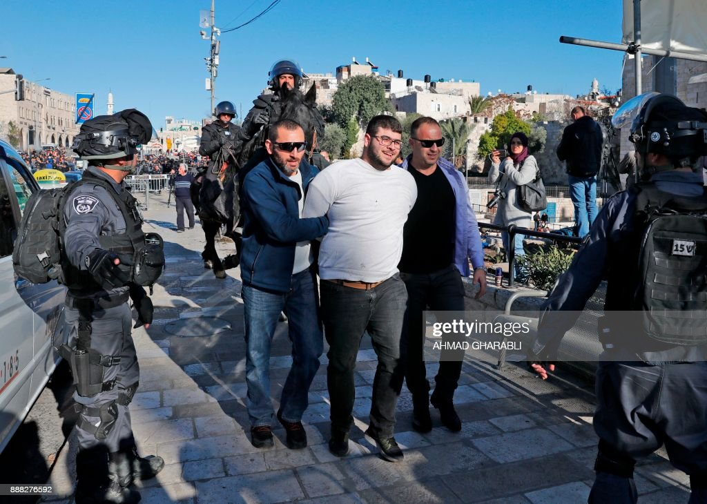 Israeli forces in plain clothes detain a Palestinian man at Damascus Gate in Jerusalem's Old City on December 8, 2017. Israel deployed hundreds of additional police officers following Palestinian calls for protests after the main weekly Muslim prayers against US President Donald Trump's recognition of Jerusalem as Israel's capital. / AFP PHOTO / Ahmad GHARABLI