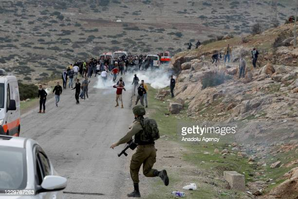 Israeli forces intervene in Palestinians with tear gas canisters during a protest against the planning of the construction of the Jewish settlement,...