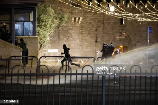 Israeli forces intervene Palestinian Muslims, who gathered in Damascus Gate after performing Tarawih prayer in Al-Aqsa Compound, with water cannon...
