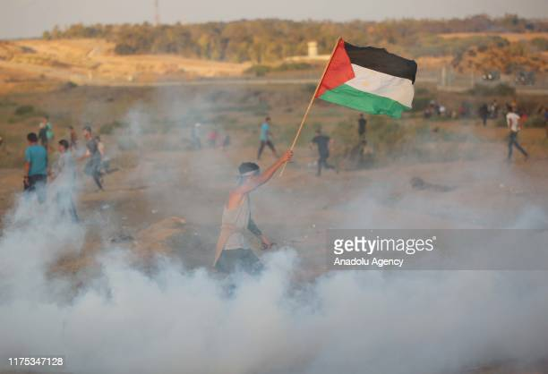"""Israeli forces intervene Palestinians with tear gas canisters during a demonstration within the """"Great March of Return"""" at Israel-Gaza border near Al..."""