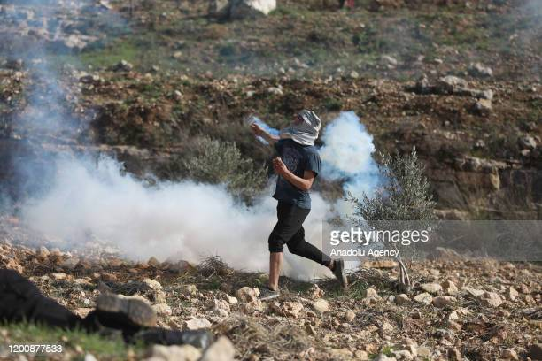 Israeli forces intervene with tear gas canisters as Palestinian youths from the village of Deir Nizam, northwest of Ramallah in the occupied West...