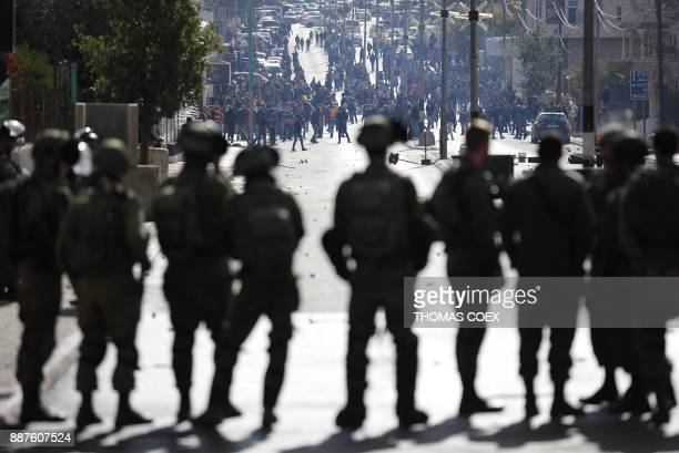 TOPSHOT Israeli forces keep watch as and Palestinian protestors throws stones and shout slogans near an Israeli checkpoint in the West Bank city of...