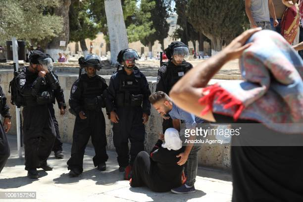 Israeli forces stand by a woman on the floor during a protest against intervention of Israeli forces after they entered East Jerusalems flashpoint...