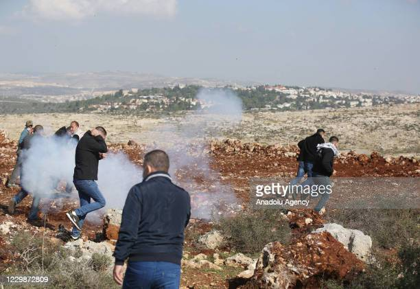 Israeli forces use tear gas as they intervene in Palestinians reacting to Jewish settlers for trying to seize agricultural lands of Palestinians in...