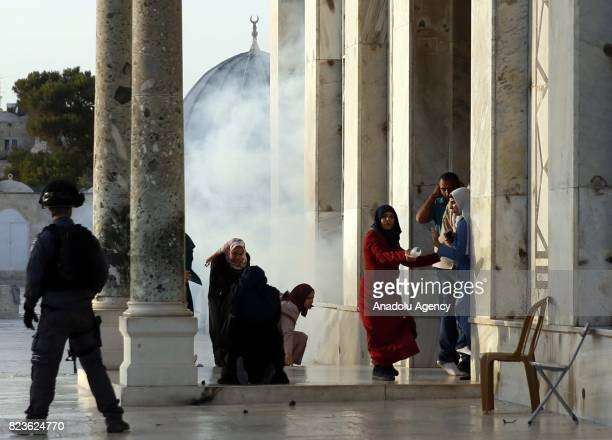 Israeli forces use tear gasses as they intervene in Palestinian worshippers as they gather to enter the Al Aqsa Mosque following the removal of...