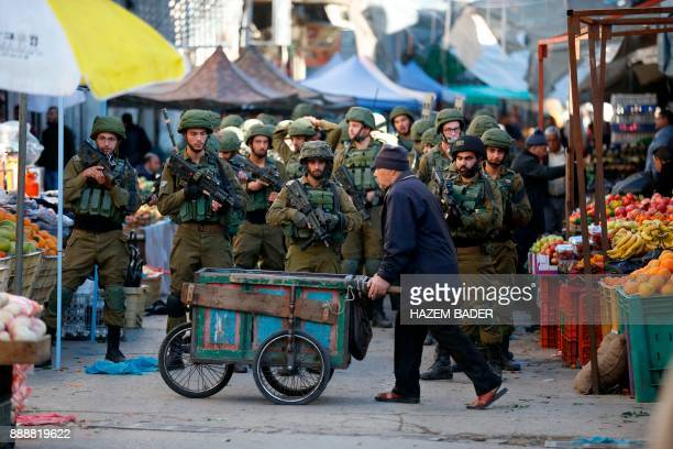 TOPSHOT Israeli forces walk down a street during clashes with Palestinian demonstrators in Hebron in the Israelioccupied West Bank on December 9...