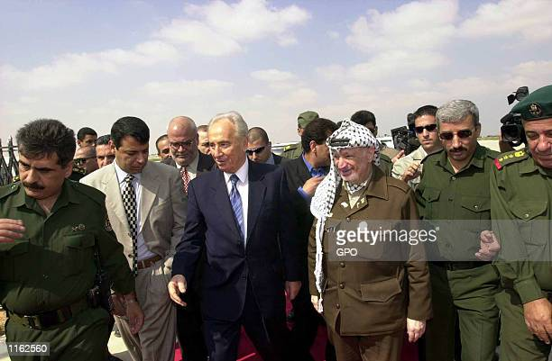 Israeli Foreign Minister Shimon Peres and Palestinian leader Yasser Arafat arrive for a meeting September 26, 2001 at the Gaza International Airport....