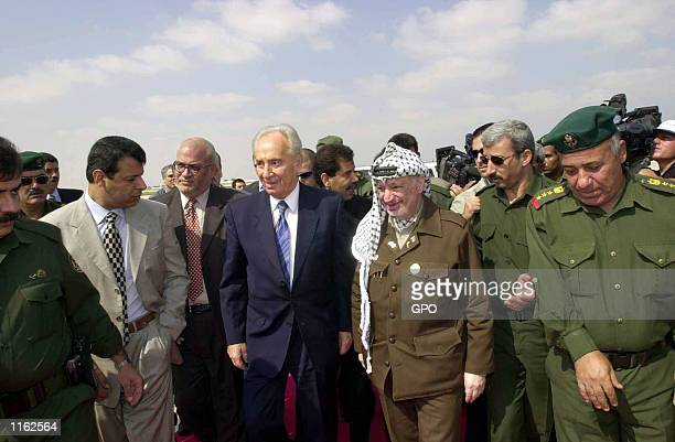Israeli Foreign Minister Shimon Peres and Palestinian leader Yasser Arafat arrive for a meeting September 26 2001 at the Gaza International Airport...
