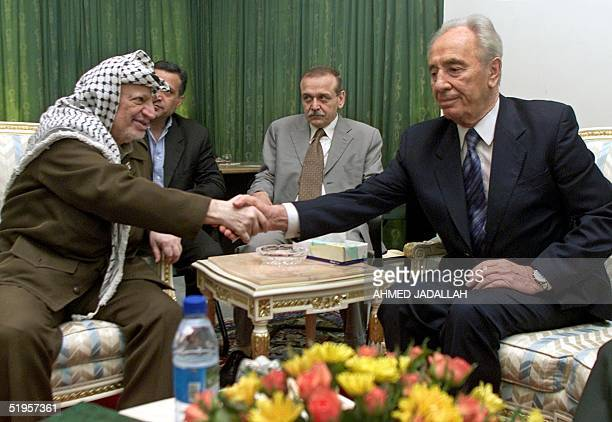 Israeli Foreign Minister Shimon Peres and Palestinian President Yasser Arafat shake hands before their meeting at the Gaza international airport 26...