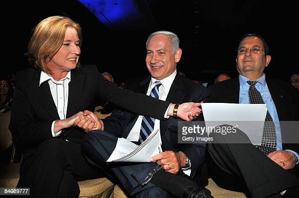 Israeli Foreign Minister Tzipi Livni shakes hands with former Prime Minister Benjamin Netanyahu and offers her hand to Defence Minister Ehud Barak...