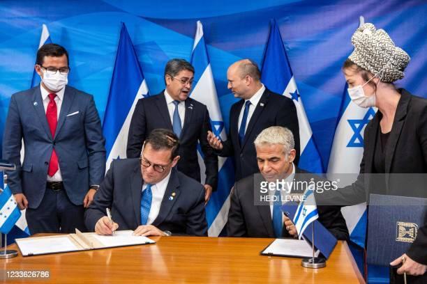 Israeli Foreign Minister Yair Lapid and Honduran Foreign Minister Lisandro sign bilateral agreements as Israeli Prime Minister Naftali Bennett speaks...