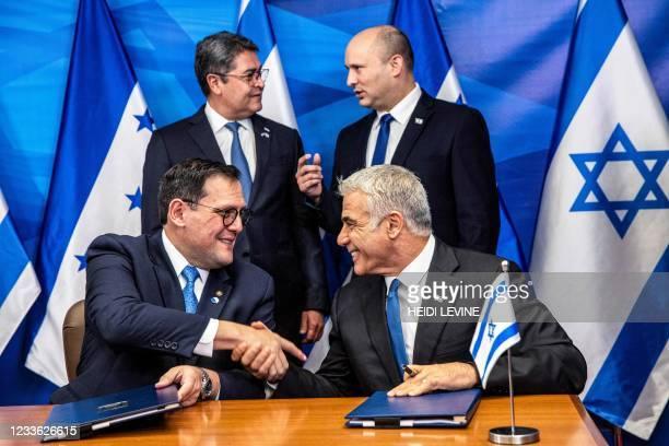 Israeli Foreign Minister Yair Lapid shakes hands with Honduran Foreign Minister Lisandro as Israeli Prime Minister Naftali Bennett speaks with...
