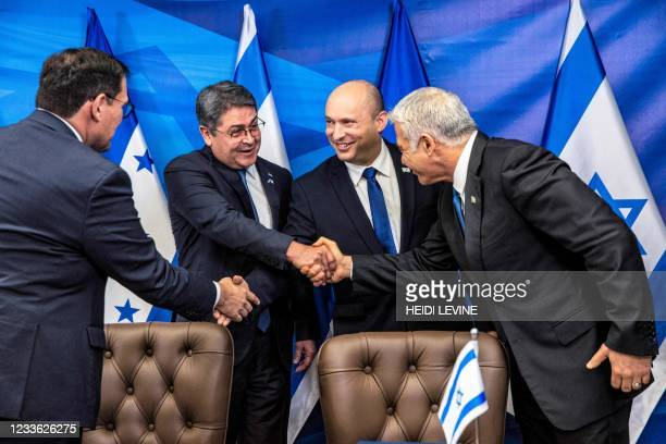 Israeli Foreign Minister Yair Lapid shakes hands with Honduran President Juan Orlando Hernandez as Israeli Prime Minister Naftali Bennett shakes...