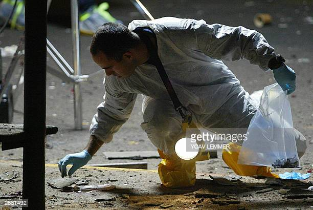 Israeli forensic expert checks the scene of a suicide bombing 25 December 2003 next to the remains of the suicide bomber who exploded himself on a...