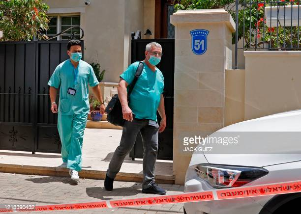 Israeli forensic experts stand at the residence of Israel's Chinese ambassador on the outskirts of Tel AViv after he was found dead on May 17, 2020....
