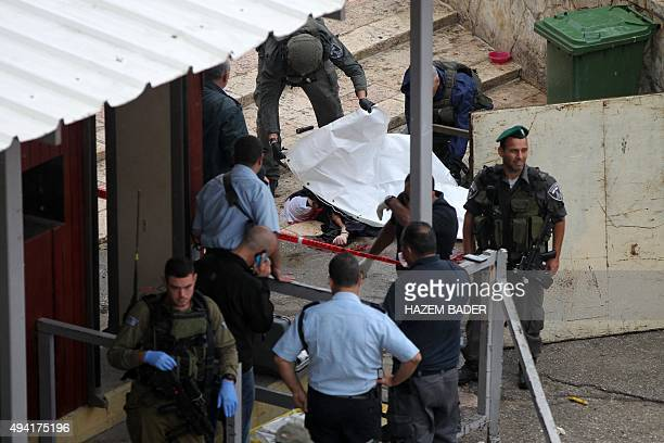 Israeli forensic policemen cover the body of a Palestinian woman who was shot dead by Israeli borderguards after attempting to stab officers at the...