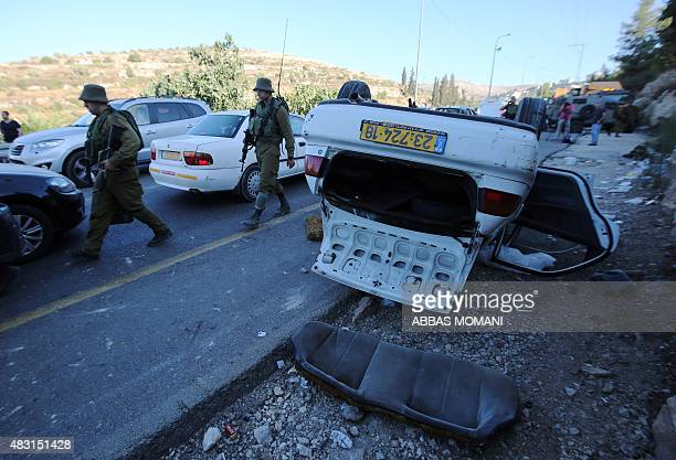 Israeli forensic policemen inspect the scene of a car attack at a junction midway between Ramallah and Nablus in the Israelioccupied Palestinian...