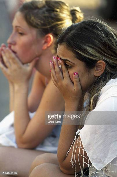 Israeli girls cry as they talk on the phone after they crossed the border into the Israeli town of Eilat from the Egyptian resort of Taba on October...