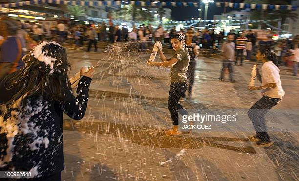 Israeli girls spray eavhothers with foam as they take part in celebrations marking Israel's Independence Day in the coastal city of Netanya on April...