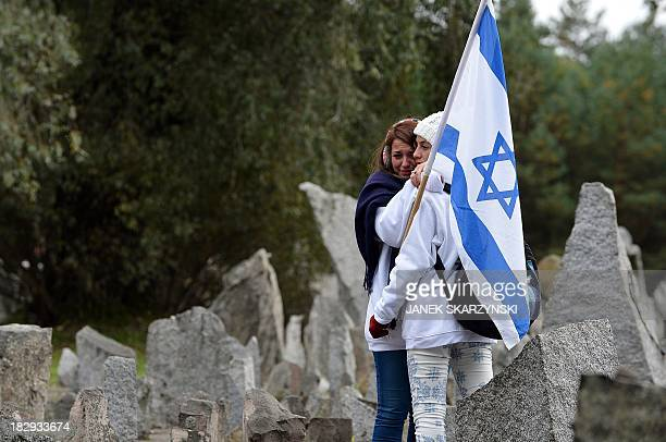 Israeli girls walk through the stones of the monument of Treblinka World War IIera Nazi death camp on October 2 2013 in Treblinka Around 600 young...