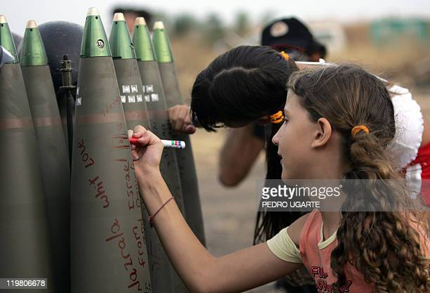 Israeli girls write messages in Hebrew on shells ready to be fire by mobile artillery unit toward Hezbollah targets in southern Lebanon 17 July 2006...