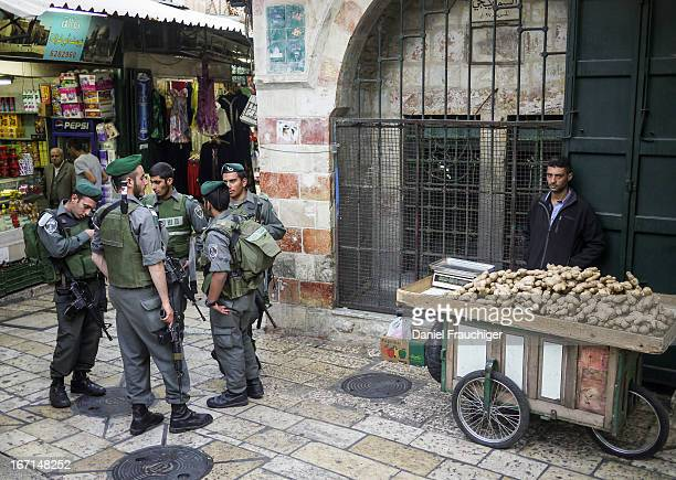 Israeli IDF soldiers next to a Palestinian vendor on April 24, 2012 in the old town of Jerusalem, Israel.
