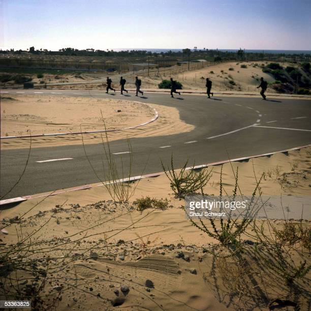 Israeli IDF soldiers run on a sandy road in the town of Rafa Yam in the Gush Katif settlement block June 14 2005 in Gush Katif Gaza Strip Throughout...